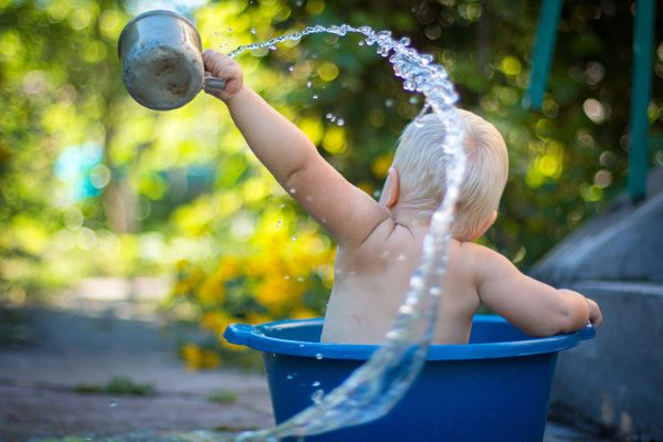 Bimbo che gioca con acqua in vasca